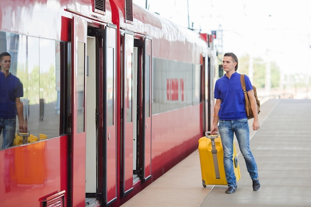 Young caucasian man with luggage at station traveling by train Premium Photo