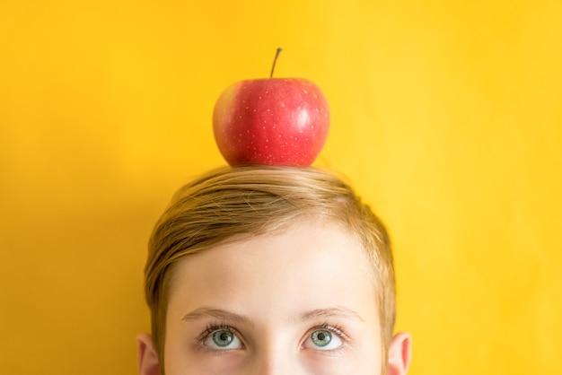 黄色の背景の上の頭の上に赤いリンゴを持つ若い白人男。ユーレカのアイデアと健康的な食事のコンセプト Premium写真