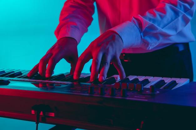 若い白人ミュージシャン、ネオンの光のグラデーションスペースで演奏するキーボード奏者。音楽、趣味、お祭りのコンセプト 無料写真