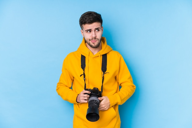 Young caucasian photographer man isolated confused, feels doubtful and unsure. Premium Photo