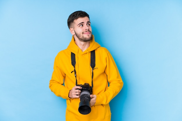 Young caucasian photographer man isolated dreaming of achieving goals and purposes Premium Photo