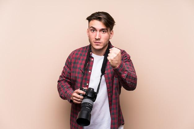 Молодой человек кавказской фотограф изолировал показывая кулак, агрессивное выражение лица. Premium Фотографии