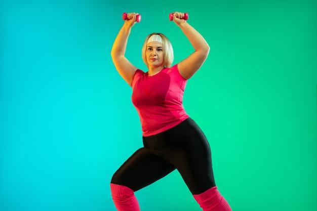 네온 불빛에 그라데이션 녹색 배경에 젊은 백인 플러스 크기 여성 모델의 교육. 무게로 운동 운동하기. 스포츠, 건강한 라이프 스타일, 신체 긍정적, 평등의 개념. 무료 사진