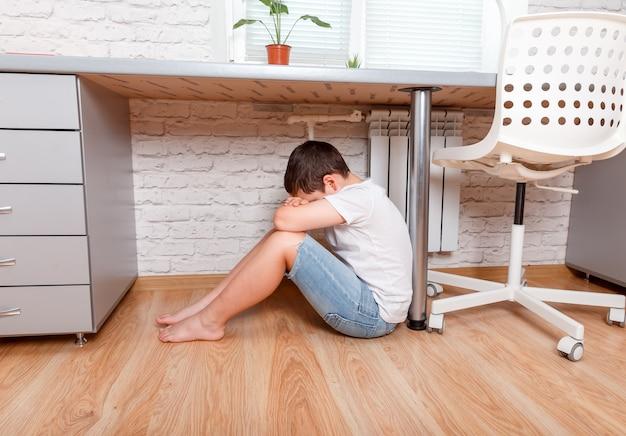 Young caucasian preteen teenage boy sitting under desk Premium Photo