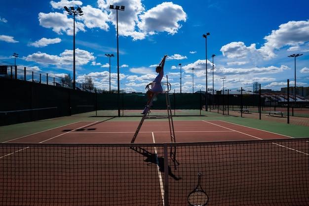 審判のはしご近くのコートで若い白人セクシーな女性テニスプレーヤー。 Premium写真