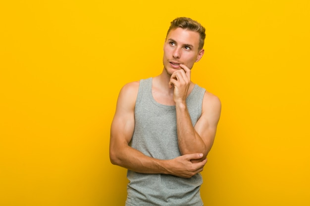 Young caucasian sport man relaxed thinking about something looking at a copy space. Premium Photo