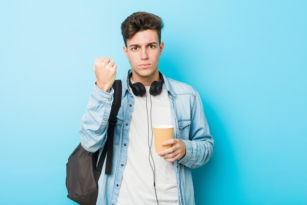 Young caucasian student man holding a take away coffee showing fist to aggressive facial expression. Premium Photo