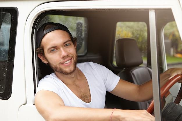 若い白人旅行者がカジュアルなtシャツと野球帽を身に着けて彼の白いスポーツユーティリティ車を運転し、遠征や夏休みを楽しんでいます。 無料写真