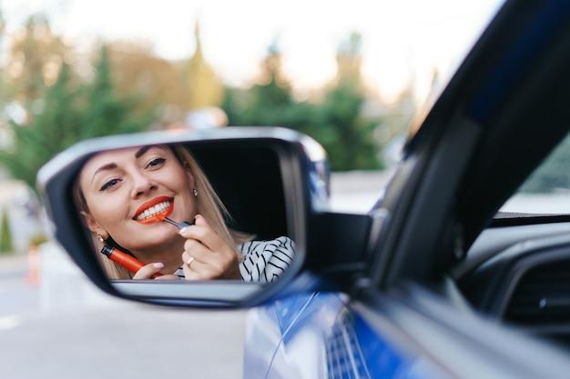 Молодая женщина кавказа, применяя помаду, глядя на отражение в зеркале автомобиля. Бесплатные Фотографии