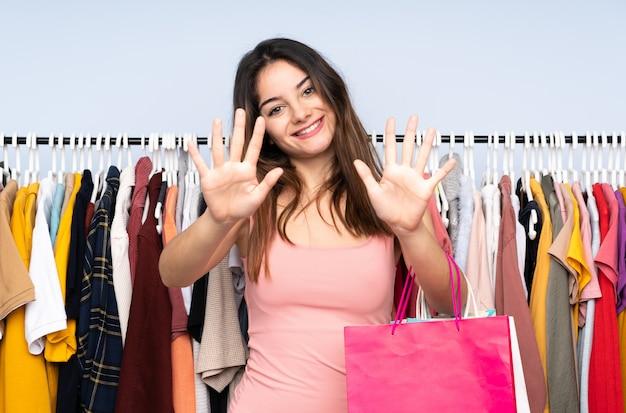 Молодая кавказская женщина покупая некоторые одежды в магазине подсчитывая 10 с пальцами Premium Фотографии