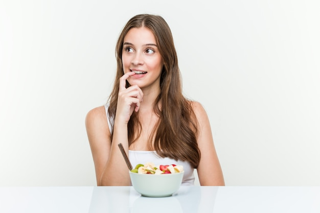Young caucasian woman eating fruit bowl relaxed thinking about something looking at a copy . Premium Photo