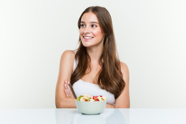 Young caucasian woman eating fruit bowl smiling confident with crossed arms. Premium Photo