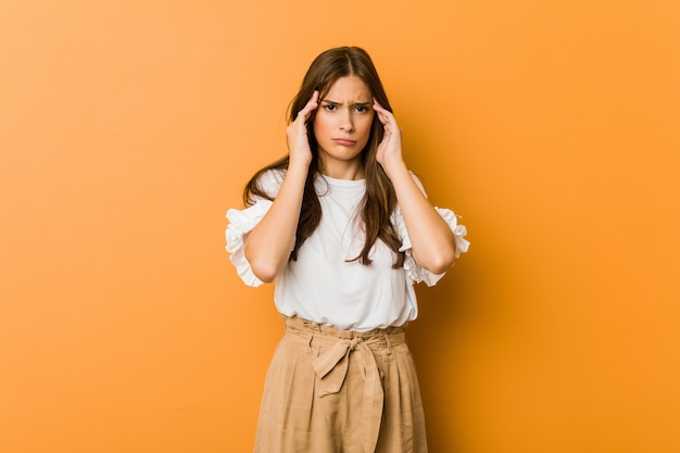 Young caucasian woman focused on a task, keeping forefingers pointing head. Premium Photo