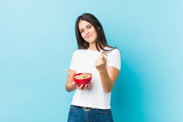 Молодая кавказская женщина держит миску с хлопьями, указывая пальцем на вас, как будто приглашая подойти ближе. Premium Фотографии