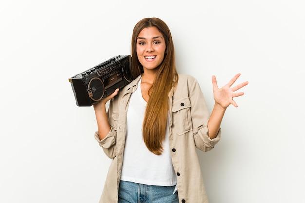 楽しい驚きを受け取って、興奮して手を上げるゲットーブラスターを保持している若い白人女性。 Premium写真