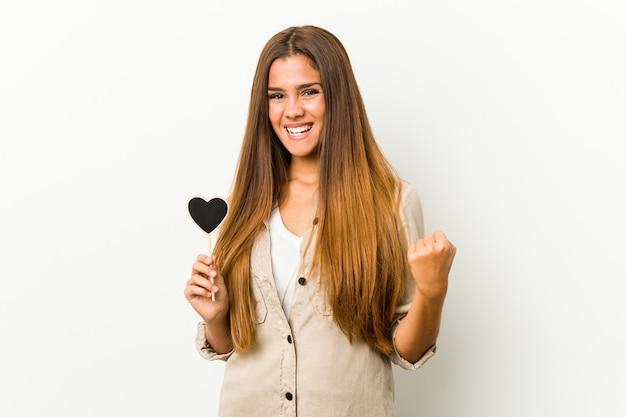 のんびりと興奮して応援するハート型の若い白人女性。利佳國際電子。 Premium写真