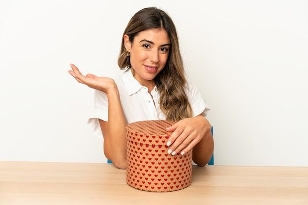 手のひらにコピースペースを示し、腰に別の手を保持している孤立したバレンタインデーボックスを保持している若い白人女性。 Premium写真