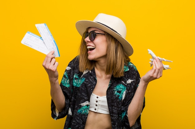 Young caucasian woman holding air tickets very happy. Premium Photo