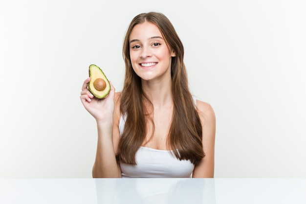 Young caucasian woman holding an avocado happy, smiling and cheerful Premium Photo