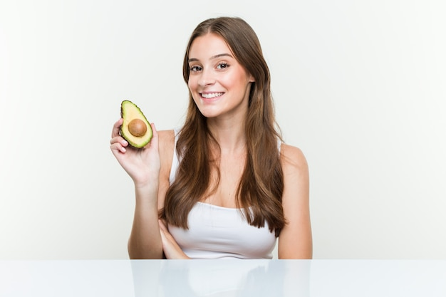 Young caucasian woman holding an avocado smiling confident with crossed arms. Premium Photo