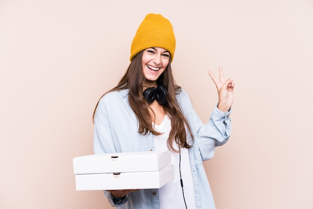 Young caucasian woman holding pizzas isolated joyful and carefree showing a peace symbol with fingers. Premium Photo