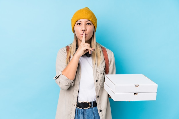 Young caucasian woman holding pizzas isolated keeping a secret or asking for silence. Premium Photo