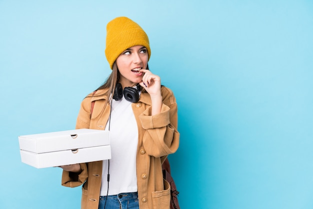Young caucasian woman holding pizzas isolated relaxed thinking about something looking at a copy space. Premium Photo
