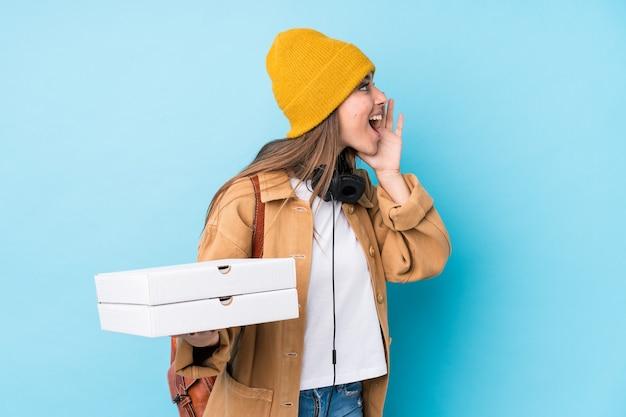 ピザを保持している若い白人女性は叫び、開いた口の近くの手のひらを分離しました。 Premium写真
