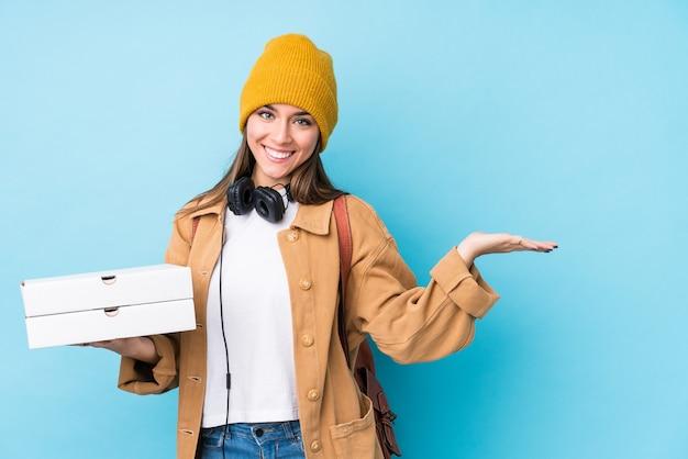 手のひらにコピースペースを示し、腰に別の手を保持している孤立したピザを保持している若い白人女性。 Premium写真