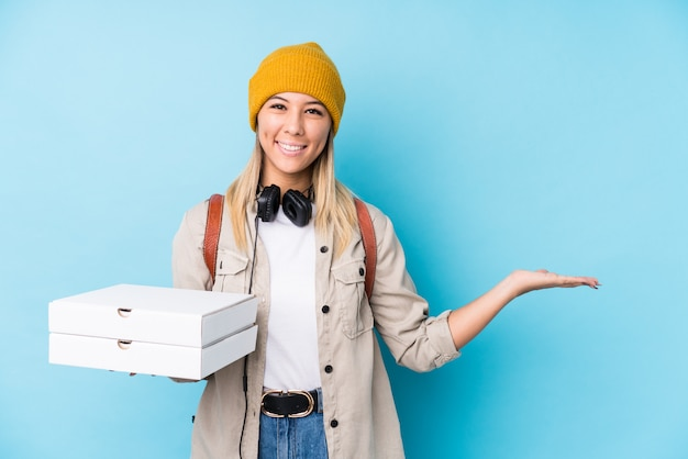 Young caucasian woman holding pizzas isolated showing a copy space on a palm and holding another hand on waist. Premium Photo