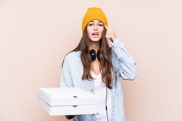 Young caucasian woman holding pizzas isolated showing a disappointment gesture with forefinger. Premium Photo