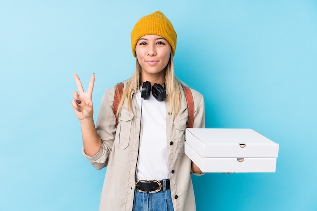 Young caucasian woman holding pizzas isolated showing number two with fingers. Premium Photo