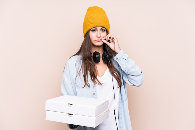 Young caucasian woman holding pizzas isolated with fingers on lips keeping a secret. Premium Photo