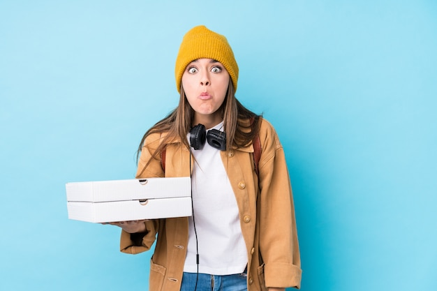 Young caucasian woman holding pizzas shrugs shoulders and open eyes confused. Premium Photo