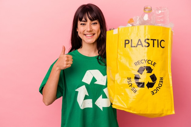 Young caucasian woman holding a recycled plastic bag isolated on pink wall smiling and raising thumb up Premium Photo