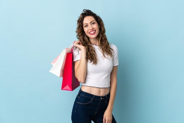 ショッピングバッグを持って笑顔の若い白人女性 Premium写真