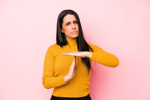 Молодая кавказская женщина изолирована на розовой стене показывая жест тайм-аута. Premium Фотографии