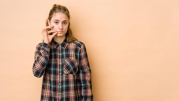 秘密を守る唇に指でベージュに分離された若い白人女性。 Premium写真