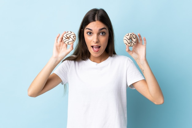 ドーナツを保持している青いで隔離され、驚いた若い白人女性 Premium写真
