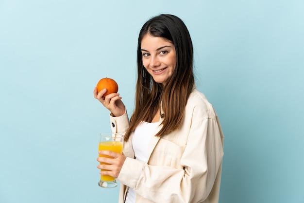 オレンジとオレンジジュースを保持している青い壁に分離された若い白人女性 Premium写真