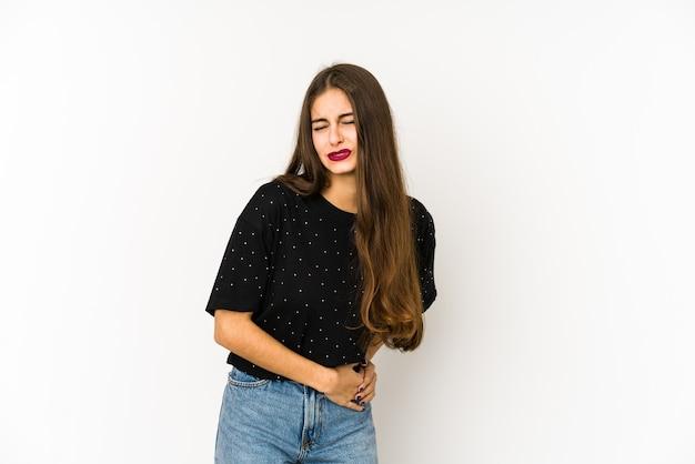 Молодая кавказская женщина, изолированная на белом, болит печень, живот. Premium Фотографии