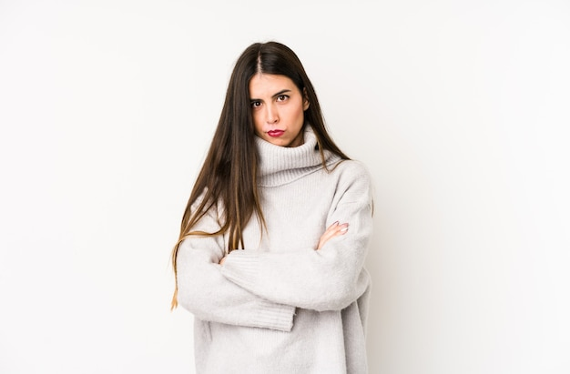 Молодая кавказская женщина, изолированная над белым, недовольно хмурясь, держит руки на груди. Premium Фотографии