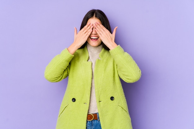 Young caucasian woman isolated on purple wall covers eyes with hands, smiles broadly waiting for a surprise. Premium Photo