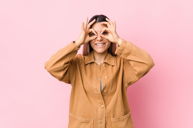 Young caucasian woman isolated showing okay sign over eyes Premium Photo