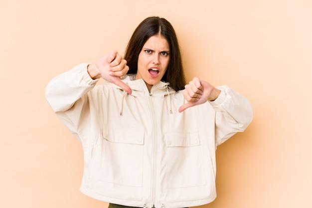 ダウン親指を示し、嫌悪感を表現するベージュの壁に若い白人女性。 Premium写真