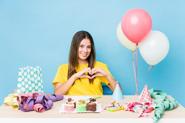笑顔と手でハートの形を示す誕生日を整理する若い白人女性。 Premium写真