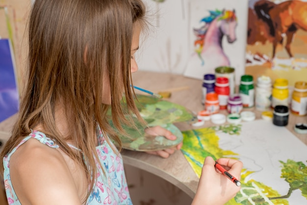 Young caucasian woman painter working in canvas in art studio Premium Photo