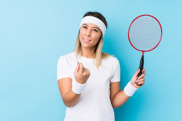 Молодая кавказская женщина, играющая в бадминтон, изолирована, указывая пальцем на вас, как будто приглашая подойти ближе. Premium Фотографии