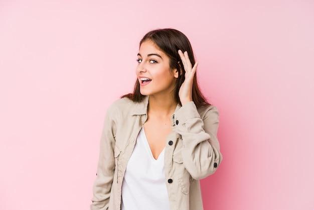 ゴシップを聞いてピンク色でポーズをとって若い白人女性。 Premium写真