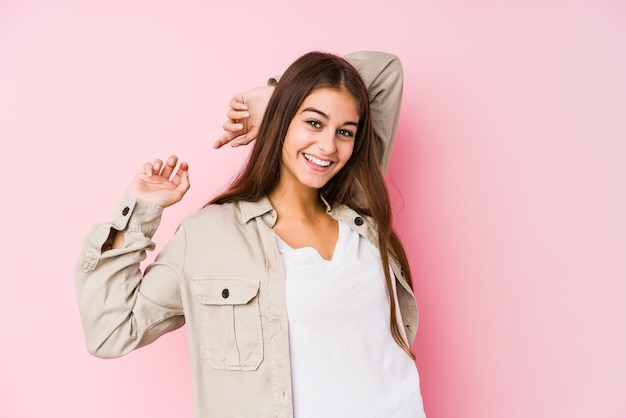 Young caucasian woman posing in a pink wall stretching arms, relaxed position. Premium Photo